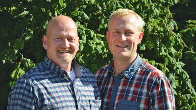 Eric Ottens und Steffen Heuer im Garten vor grüner Hecke