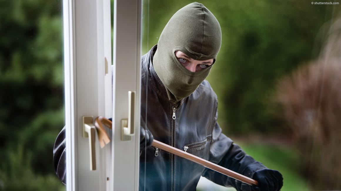Einbrecher versucht durch ein Fenster einzubrechen